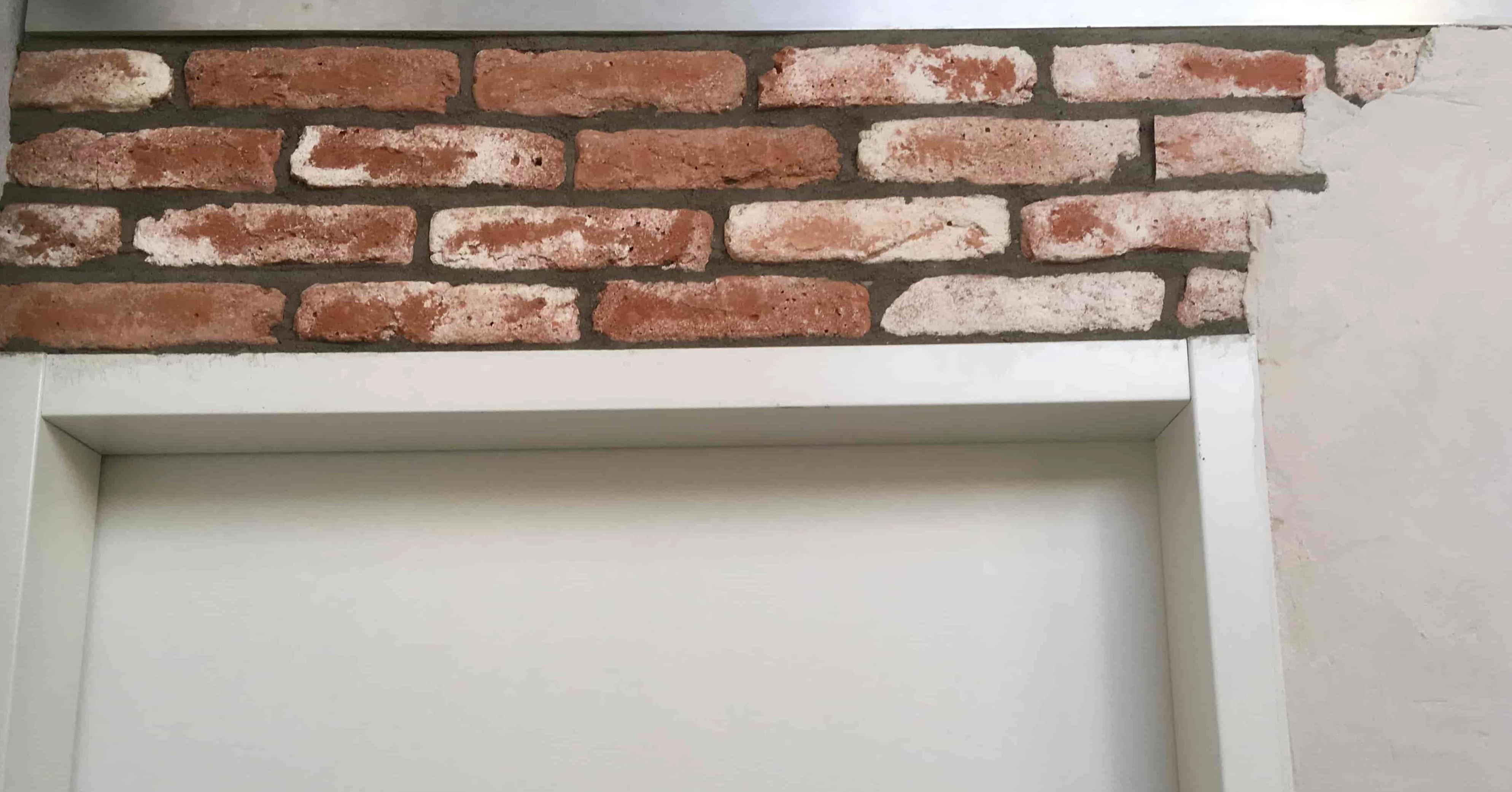 Oude bakstenen muur boven een deur, met donkere voeg en stuclaag waardoor het lijkt dat de muur achter een stuclaag vandaan is gekomen