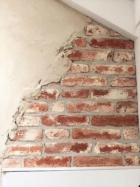 Oude bakstenen muur in een hoek op zolder, boven een kastje, met grijze voeg en stuclaag waardoor het lijkt dat de muur achter een stuclaag vandaan is gekomen