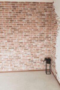 Stenen muur in de woonkamer met dunne steenstrips van Wall of Steen met stucwerk