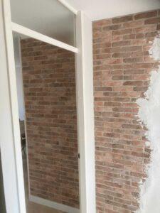 bakstenen muur met stucwerk door Wall of Steen met dunne bakstenen voor verweerde stenen muur in de hal