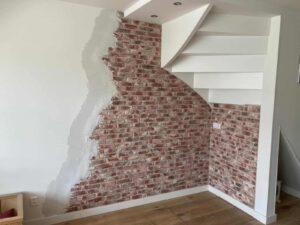 muur woonkamer met stuc over steenstrips brickwall door Wall of Steen voor een oude bakstenen muur