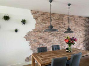 woonkamer muur met verweerde steenstrips van Wall of Steen met stucwerk en oude dunne bakstenen